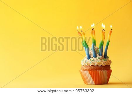 Birthday cupcake with candles on color background