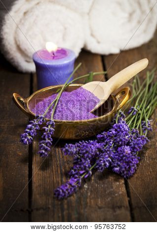 Lavender bath salt in brass bowl, fresh flowers, scented candle and towels
