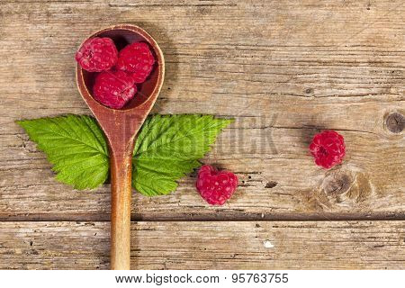 raspberries on a spoon with leaves resembling wings, rustic wood background, top view