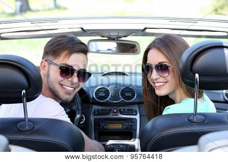 Young pretty couple in cabriolet, outdoors