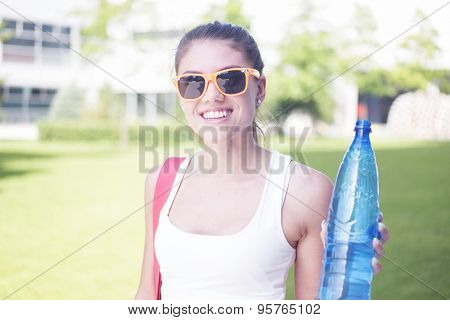 Close up Pretty Young Woman in a Summer Outfit at the Park, Holding a Plastic Bottle of Water and Smiling at the Camera.