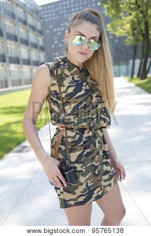 Stylish Pretty Young Blond Woman Wearing Trendy Camouflage Dress and Sunglasses with Binoculars, Standing at the Pathway.