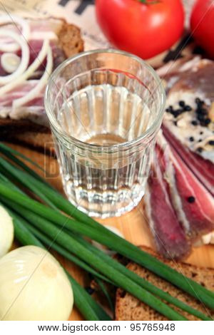 Vodka and smoked meat on wooden table