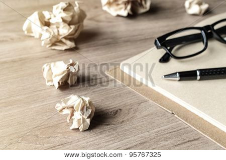 Crumpled Paper Balls With Eye Glasses And Notebook On Wooden Desk
