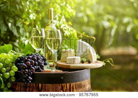 Old wooden barrel with bottle and glass of red wine.