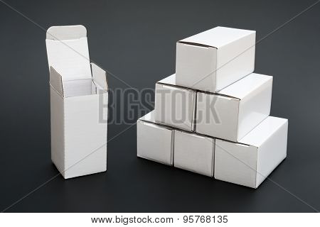 Several White Boxes With One Opened And Ther Other Closed On Black