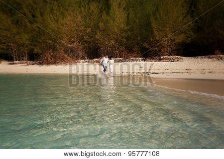 Bride And Groom  Splash At Sea Edge Against Trees