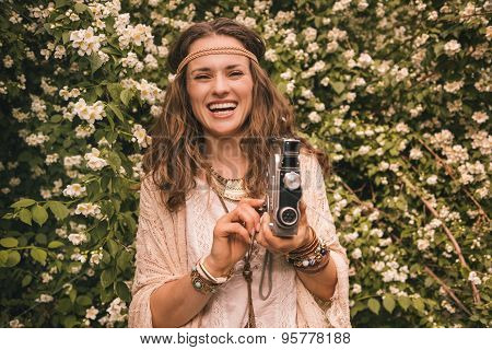 Smiling Boho Young Woman Among Flowers With Retro Camera