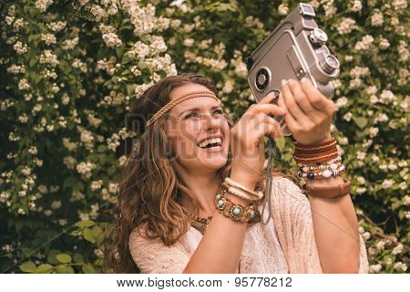Happy Bohemian Young Woman Among Flowers Playing With Retro Came