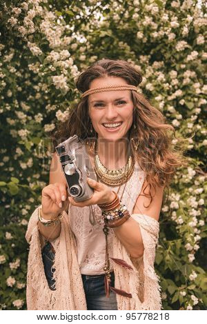 Smiling Hippie Young Woman Among Flowers With Retro Camera