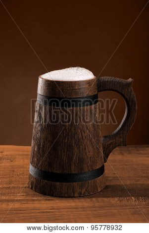 Mug Of Fresh Beer With A Cap Of Foam On A Dark Background.