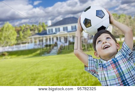 Cute Smiling Young Boy Holding Soccer Ball In Front of Beautiful House.