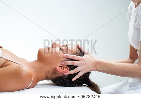 Therapist Doing Healing Osteopathic Treatment On Woman.