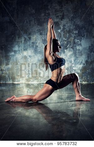 Strong woman bodybuilder stretching on wall background. Dark contrast colors.
