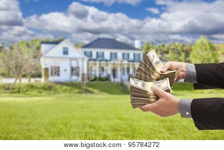 Man Handing Over Thousands of Dollars in Front of Beautiful House.