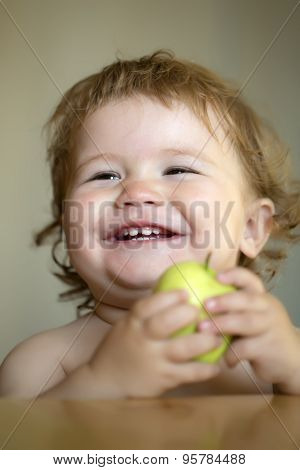 Portrait Of Laughing Baby Boy With Apple