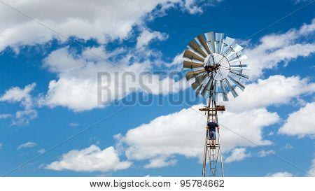 Man Climbing A Windmill