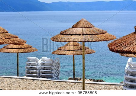 Umbrellas On A Beach With Clear Water And Blue Slippers