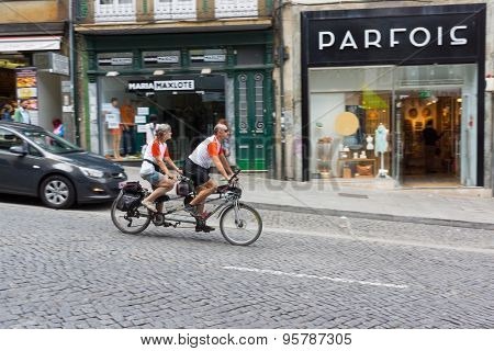 PORTO, PORTUGAL - JUNE, 12: Mature couple ride tandem bicycle in old city on June 12, 2015 in Porto, Portugal