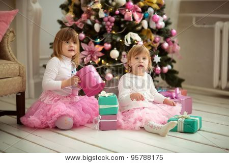 sisters with gifts by the Christmas tree