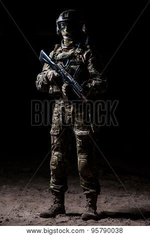 Soldier In Camouflage With A Rifle Standing On A Platoon And Watches