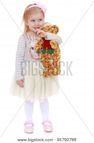 Very little blond Caucasian girl dressed in a beautiful white dr