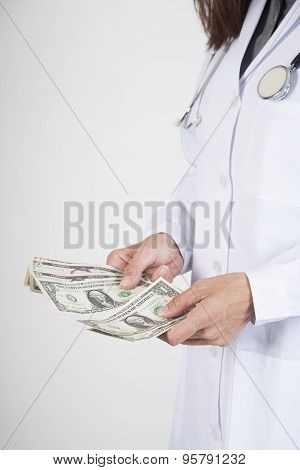 Doctor Counting Dollar Banknotes