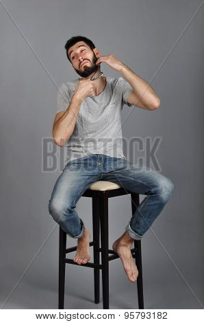 Man sitting on a chair and shaves his beard with scissors