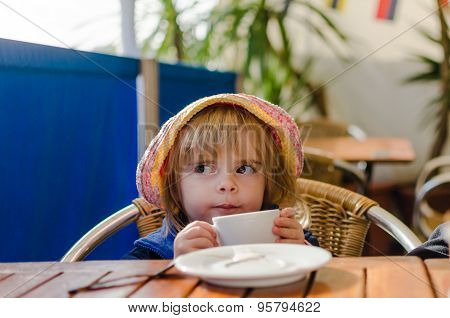 Little White Caucasian Blonde Girl Wearing Pink Summer Hat Sitting At The Table Drinking Warm Milk F