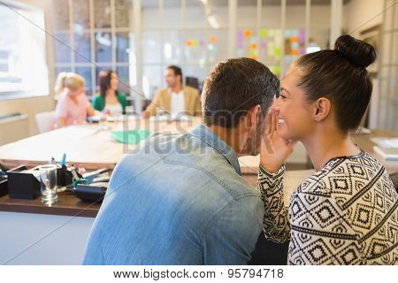 Casual businesswoman whispering secret to her colleague in the office