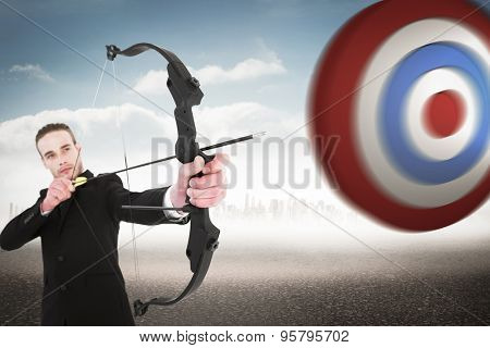 Concentrated businessman shooting a bow and arrow against city on the horizon