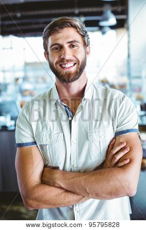 Young man with arms crossed looking the camera at the cafe