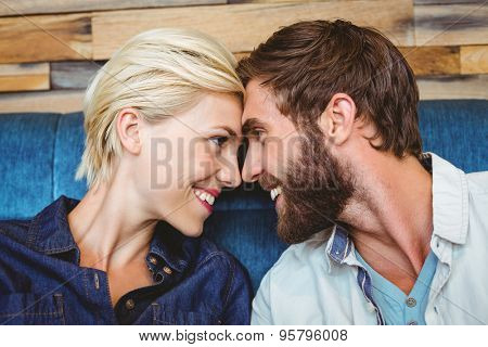 Cute couple on a date giving head to head at the cafe