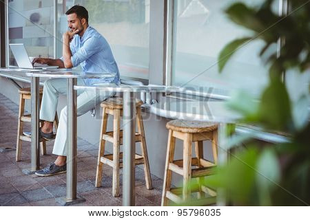 Distant view of a thoughtful businessman using his laptop outside the cafe