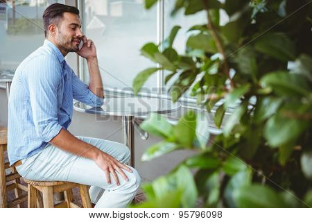 Distant view of businessman on the phone outside the cafe