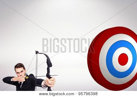 Smart businessman practicing archery looking at camera against white background with vignette