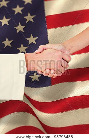 Extreme closeup of a doctor and patient shaking hands against beige