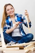 pic of enthusiastic  - Woman assembling wooden furniture using screwdriver - JPG