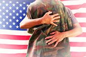 picture of reunited  - Solider reunited with father against rippled us flag - JPG