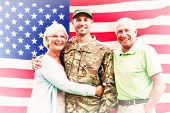image of reunited  - Soldier reunited with parents against rippled us flag - JPG