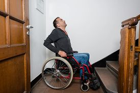 picture of panic  - a disabled man in a wheelchair is facing a barrier of stairs - JPG