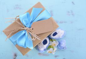 foto of teething baby  - Baby shower Its a Boy natural wrap gift with gift box baby booties and dummy on pale blue shabby chic rustic wood table - JPG