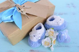 picture of teething baby  - Baby shower Its a Boy natural wrap gift with gift box baby booties and dummy on pale blue shabby chic rustic wood table - JPG