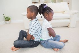 picture of not talking  - Siblings not talking to each other at home in the living room - JPG