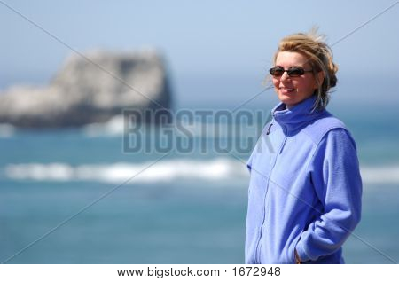 Woman Stands Along Rugged Coastline