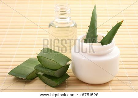 jar of aloe cream bttle of oil and fresh aloe vera - beauty treatment