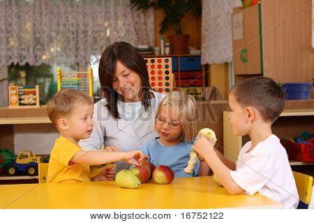 teacher and three preschoolers having break for fruits