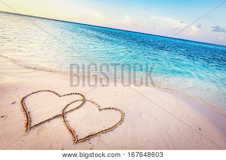 Two hearts drawn on sand