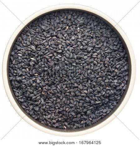 black cumin seeds (Nigella sativa) in a round ceramic bowl isolated on white