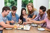 Happy young friends enjoying wine and sushi at home poster